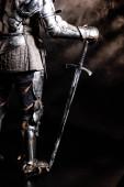 Ausgeschnittene Ansicht eines Ritters in Rüstung mit Schwert auf schwarzem Hintergrund