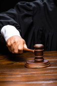 ostříhaný pohled na soudce v soudní róbě sedí u stolu a mlátí kladívkem izolovaným na černém