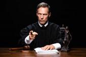 soudkyně v soudní róbě sedící u stolu a ukazující prstem izolovaným na černé