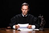 soudkyně v soudní róbě sedí u stolu a čtení papíru izolované na černém
