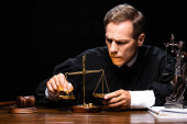 judge in judicial robe sitting at table and holding scales of justice isolated on black