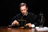 soudkyně v soudní róbě sedí u stolu a drží stupnice spravedlnosti izolované na černé
