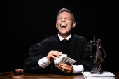 smiling judge in judicial robe sitting at table and holding dollar banknotes isolated on black