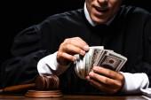oříznutý pohled na šokovaného soudce v soudní róbě sedícího u stolu a počítajícího dolarové bankovky izolované na černém