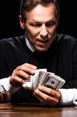 soudkyně v soudním županu sedí u stolu a počítá dolarové bankovky izolované na černém