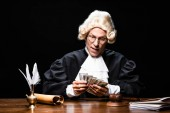 judge in judicial robe and wig sitting at table and counting money isolated on black