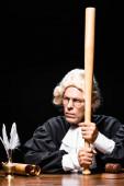 soudkyně v soudní župan a paruka sedí u stolu a drží pálku izolované na černé