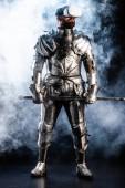 Ritter mit Virtual-Reality-Headset in Rüstung mit Schwert auf schwarzem Hintergrund