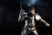 schöner und wütender Ritter in Rüstung, der mit Schwert auf schwarzem Hintergrund kämpft