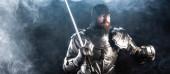 Panoramaaufnahme eines gutaussehenden Ritters in Rüstung, der wegschaut und das Schwert auf schwarzem Hintergrund hält