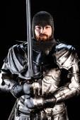 schöner Ritter in Rüstung, der in die Kamera schaut und Schwert isoliert auf Schwarz hält