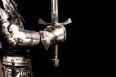 Ausgeschnittene Ansicht eines Ritters in Rüstung mit Schwert isoliert auf schwarz