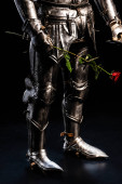 cropped view of knight in armor holding rose on black background