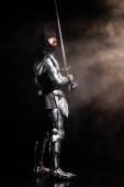 schöner Ritter in Rüstung mit Schwert auf schwarzem Hintergrund