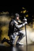 schöner Ritter in Rüstung mit Schwert und Kniekehle auf schwarzem Hintergrund