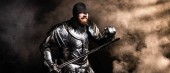 panoramic shot of handsome knight in armor holding sword and fighting on black background
