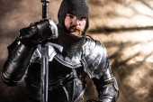 handsome knight in armor holding sword on black background