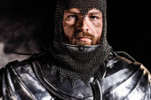 handsome knight in armor looking at camera on black background