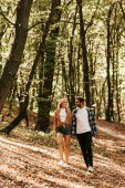mosolygó fiatal pár fogja egymás kezét, és nézik egymást, miközben sétálnak a parkban