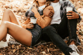 cropped view of young couple holding thermo cups while sitting on fall foliage