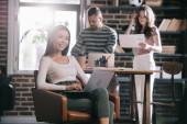 Lächelnde Geschäftsfrau sitzt im Sessel, benutzt Laptop und lächelt in die Kamera neben jungen Kollegen
