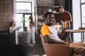 jóképű afro-amerikai üzletember kezében kávé menni, miközben ül karosszékben közelében fiatal multikulturális kollégák