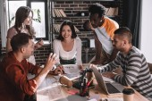young, positive multicultural businesspeople brainstorming near desk in office
