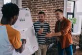 mladí multikulturní podnikatelé stojící u flipchartu s infografií a diskutují o podnikatelských nápadech