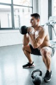 Photo handsome and shirtless sportsman squatting with weight in sports center