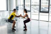 Seitenansicht des Sportlers und der Sportlerin beim gemeinsamen Kniebeugen im Sportzentrum