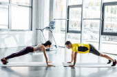 Photo sportsman and sportswoman doing plank on fitness mats in sports center