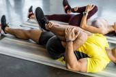 Fotografie oříznutý pohled na sportovce a sportovkyni roztahující se na fitness podložky ve sportovním centru