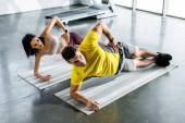 sportovec a sportovkyně dělají prkno na fitness podložky ve sportovním centru