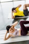 sportovec a sportovkyně dělají křupky na fitness podložky ve sportovním centru