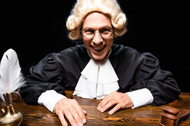 Smiling judge in judicial robe and wig sitting at table isolated on black stock vector