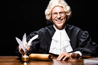 Smiling judge in judicial robe and wig taking feather isolated on black stock vector
