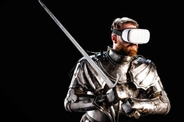 Knight with virtual reality headset in armor holding sword isolated on black stock vector
