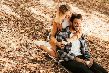 Happy girl embracing cheerful boyfriend while sitting on fall foliage in park stock vector