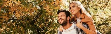 Panoramic shot of cheerful man piggybacking happy girlfriend in park stock vector