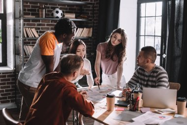 young multicultural businesspeople discussing business ideas near desk in office