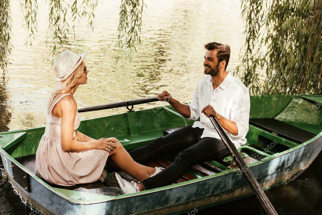 giovane donna in prendisole con fidanzato felice seduta in barca sul lago