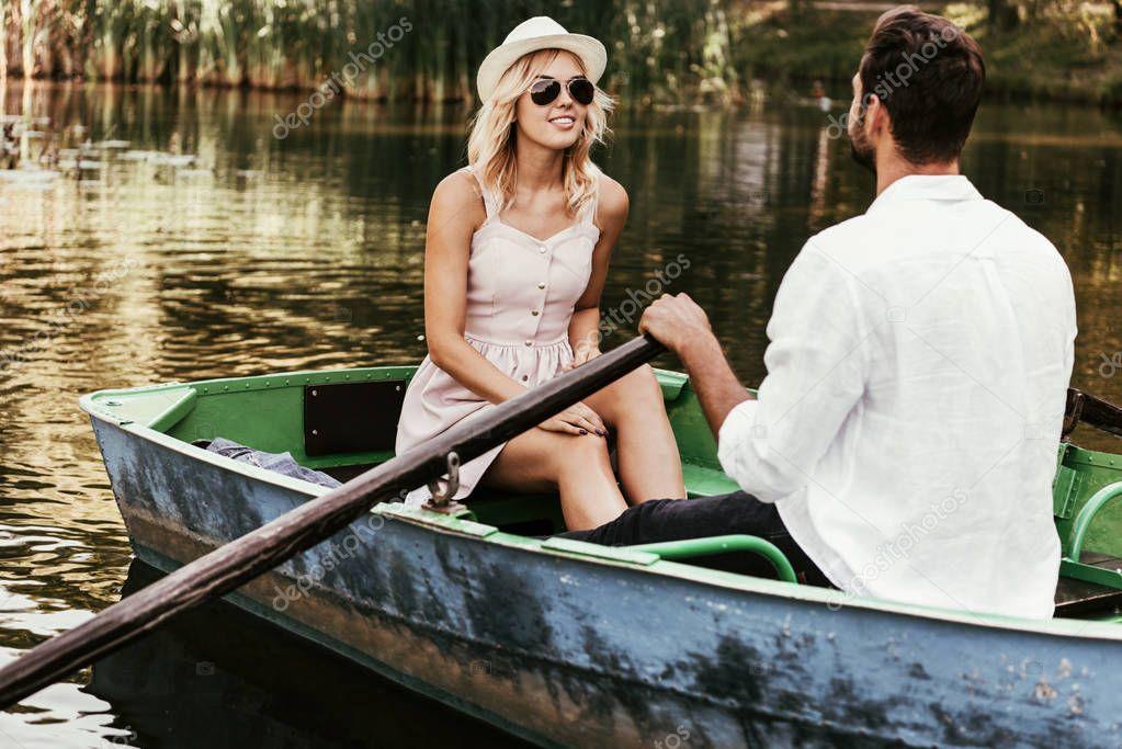 sorridente ragazza in sundress e occhiali da sole guardando fidanzato in barca