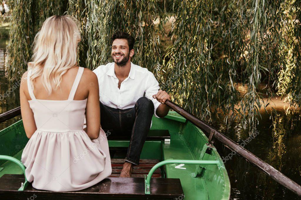 vista posteriore di giovane donna seduta in barca vicino fidanzato felice