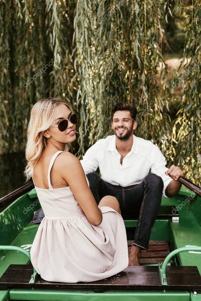 attraente giovane donna guardando la fotocamera mentre seduto in barca vicino fidanzato felice