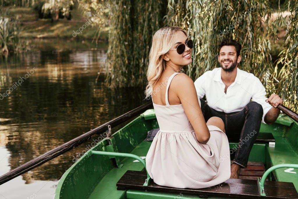 allegra giovane donna guardando la fotocamera mentre seduto in barca vicino fidanzato felice