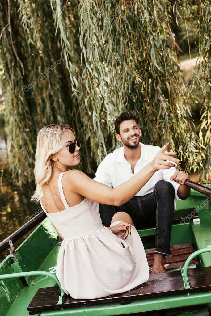 attraente giovane donna che punta con il dito mentre seduto in barca vicino fidanzato felice