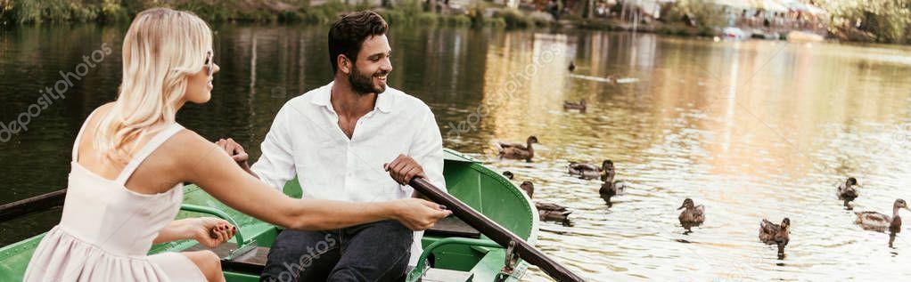 colpo panoramico di giovane coppia in barca sul lago vicino a gregge di anatre