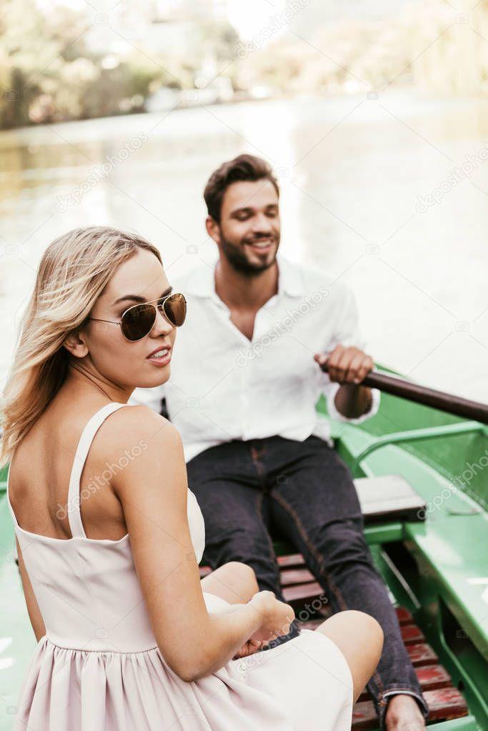 attraente ragazza in occhiali da sole guardando la fotocamera mentre seduto in barca con il fidanzato