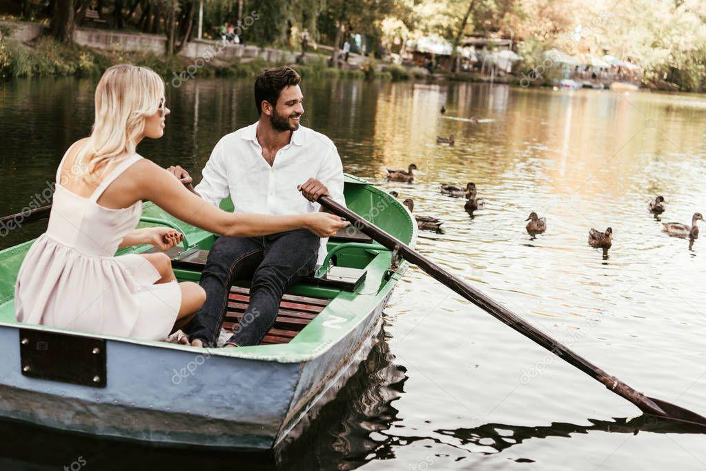 felice giovane coppia in barca sul lago vicino fiocco di anatre