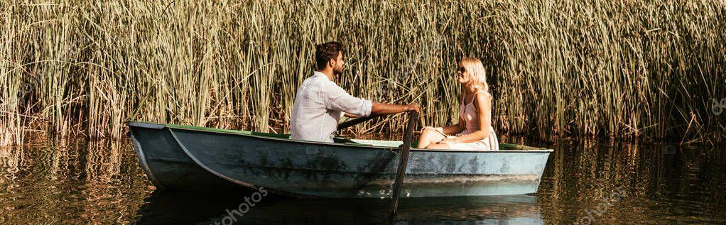 colpo panoramico di coppia giovane in barca su fiume vicino a boscaglia di carice
